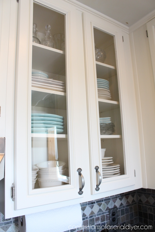 Up close of the glass doors with plates and bowls in the cabinet.