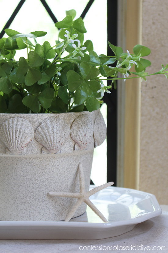 Give a terra cotta pot a beachy makeover with faux stone spray paint and scallop shells!