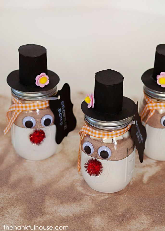 Snowman Soup Gift Jars with black hats and red noses on the counter.