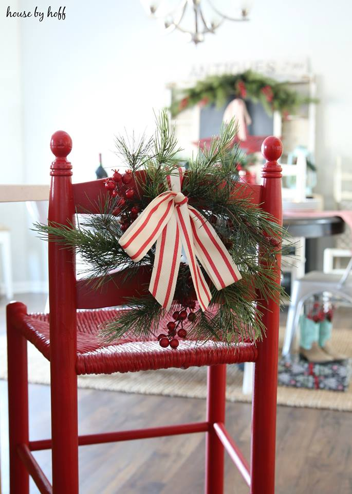 A red bar chair with a red and white bow and sprigs of greenery.