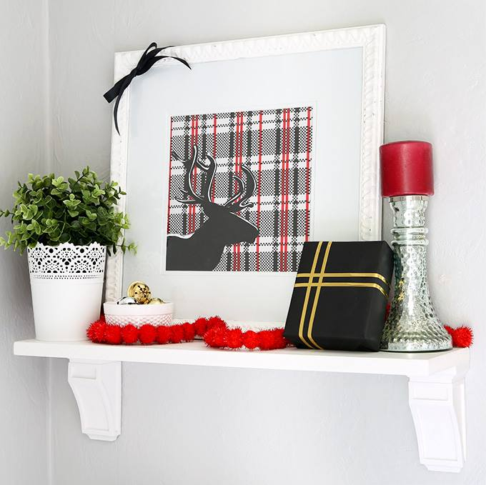 A picture of a reindeer in black with a plaid background, and candles on the mantel to.