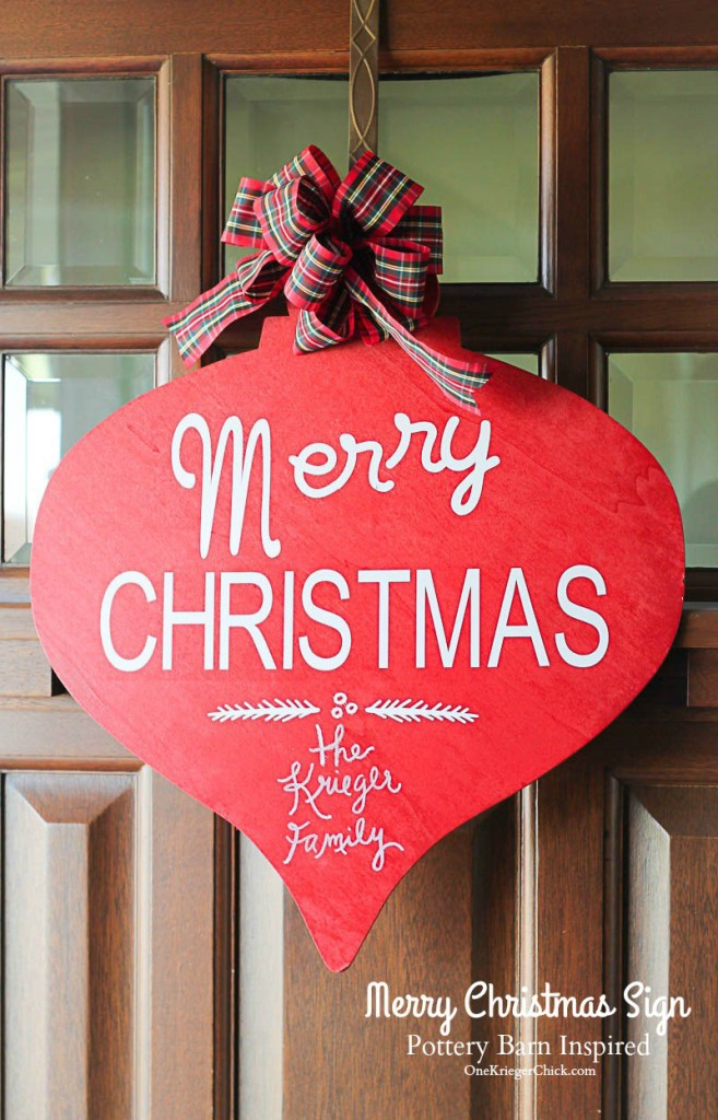 Merry Christmas Sign in red with a plaid bow hanging on the door.