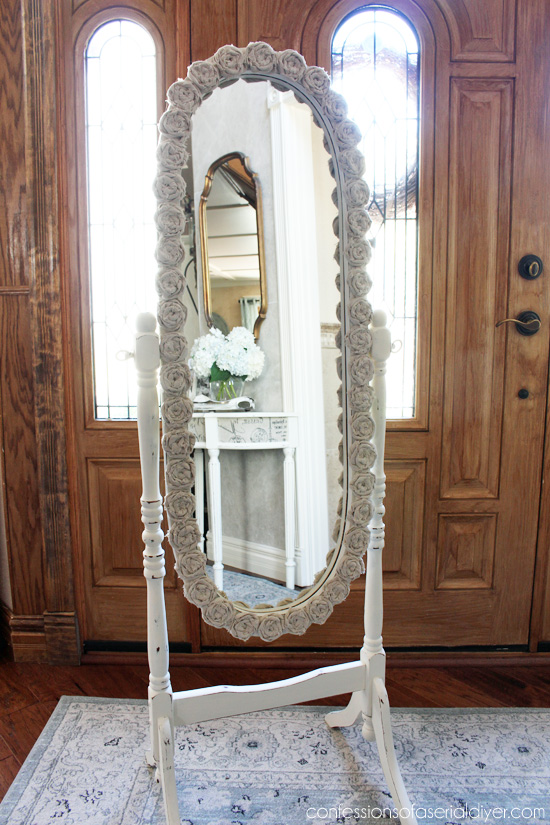 Stanidng oval mirror with dropcloth rosettes.