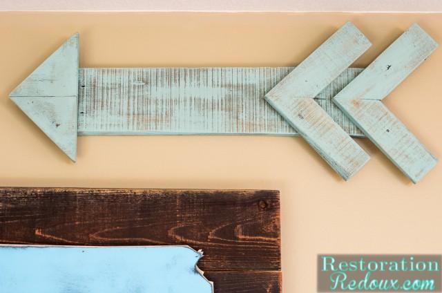 A light blue wooden arrow made from a pallet.