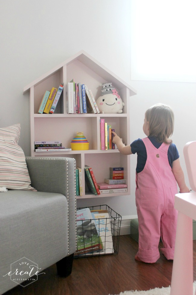 A little girl looking at her bookshelf in her room.