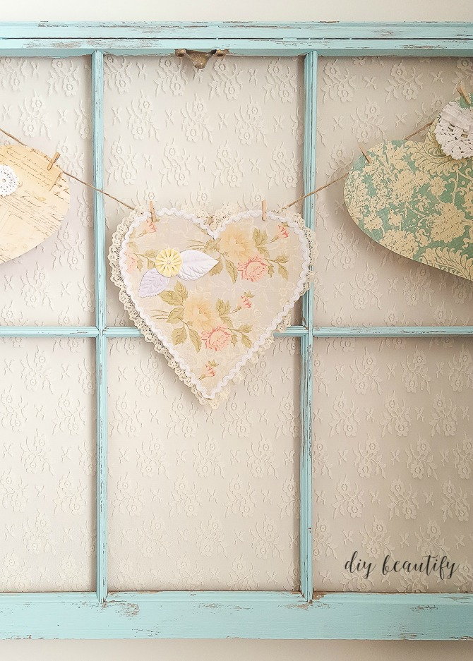 A light blue antique window frame with a string of paper hearts on it.