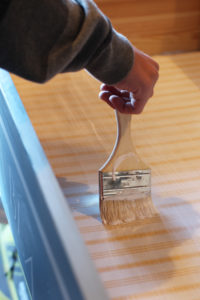 A chip brush and Mod Podge are perfect for adding fabric to drawers