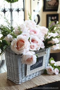 Faux camellias and miniature roses make the perfect Spring centerpiece in this basket. confessionsofaserialdiyer.com