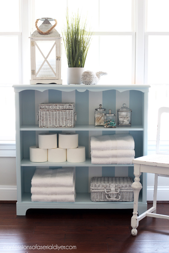 $15 yard sale bookcase painted with blue and white stripes from confessionsofaserialdiyer.com
