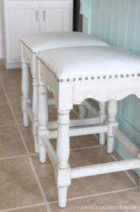 Barstools covered in white vinyl with chrome nailhead trim from confessionsofaserialdiyer.com