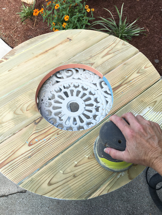 Sanding away paint using a rotary sander.
