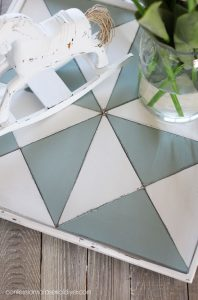 Cut pieces of luan to fit the bottom of a tray to create a quilt-inspired look.