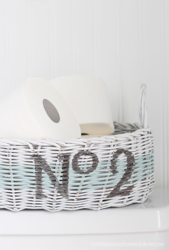 Thrift store basket made over to hold TP from confessionsofaserialdiyer.com