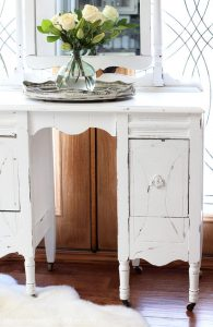 Close up of thrift store dressing table painted white and distressed