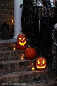 Jack-o-Lanterns and teal lights in mason jars light the steps.