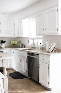 White painted kitchen with beadboard cabinets