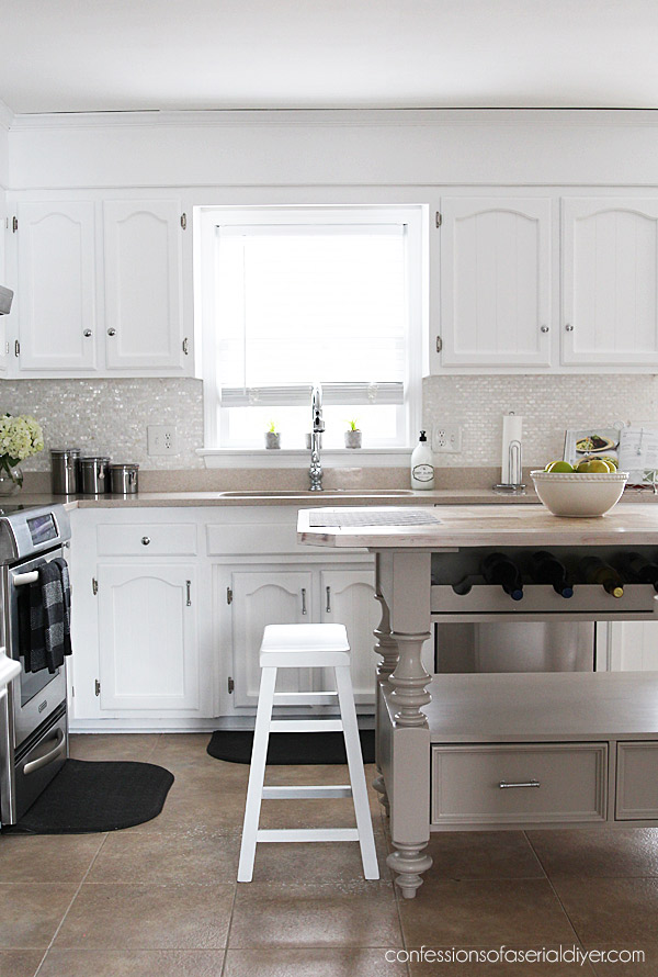 White painted kitchen with bead board cabinets