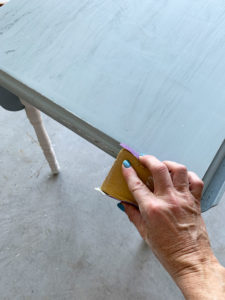 Wrap a piece of sandpaper around an old foam sanding sponge to make it easier to handle.